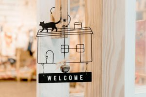 business welcome sign on shop door with house and cat