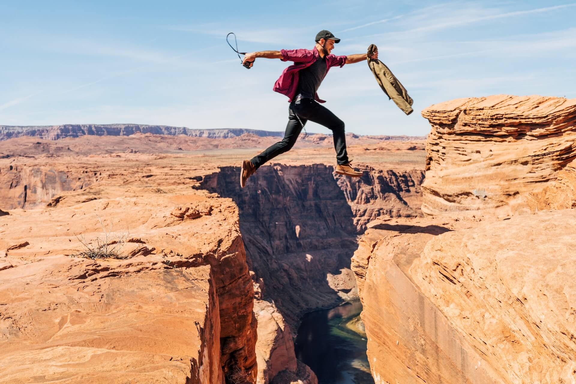 man jumping over cliff representing determination to start a business